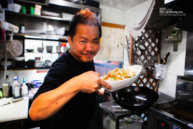 出来上がった野菜炒めの皿を「どうだ」と見せられるも、今日も訪れるお客さん達の食の幸せを支える師匠のたくましい腕ばかりが目立つのでした。