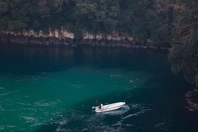 遊歩道から下をみやると、船の上で釣りをしている人。