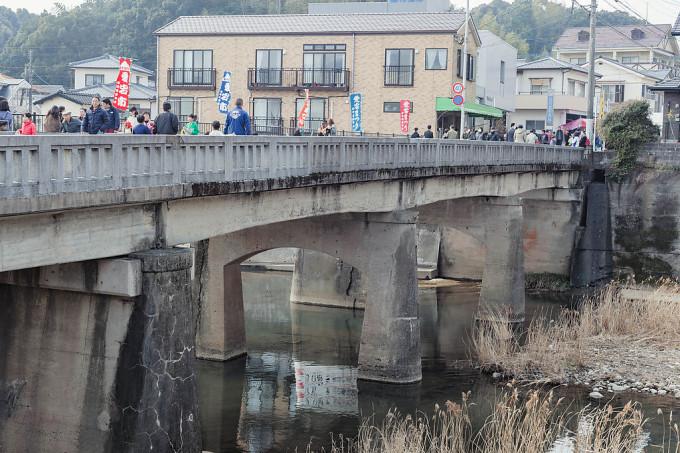 相浦川にかかる橋をわたり祭りに行き交う人々