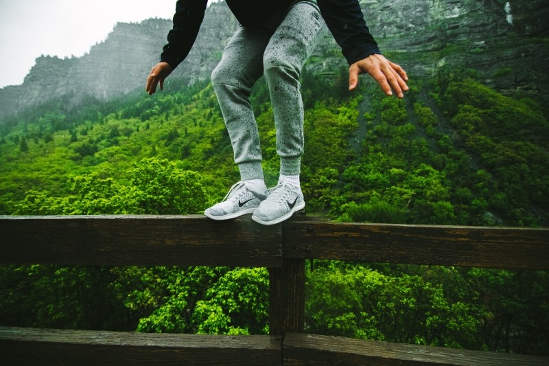 young-man-standing-on-fence-with-bush-and-mountains-in-background