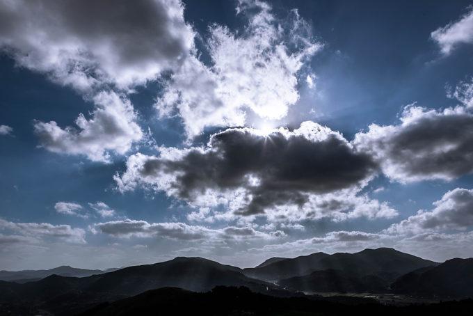 山頂から望む山間の畑にさす光が美しい