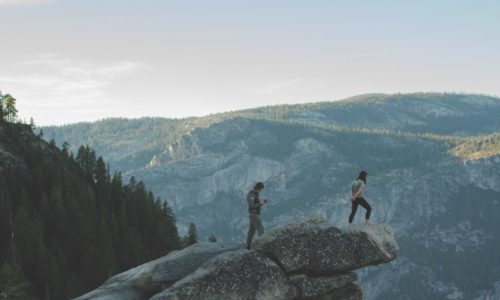 tourists-standing-on-rocks-in-mountains