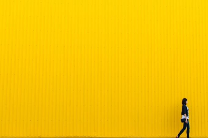 woman-walking-against-yellow-wall