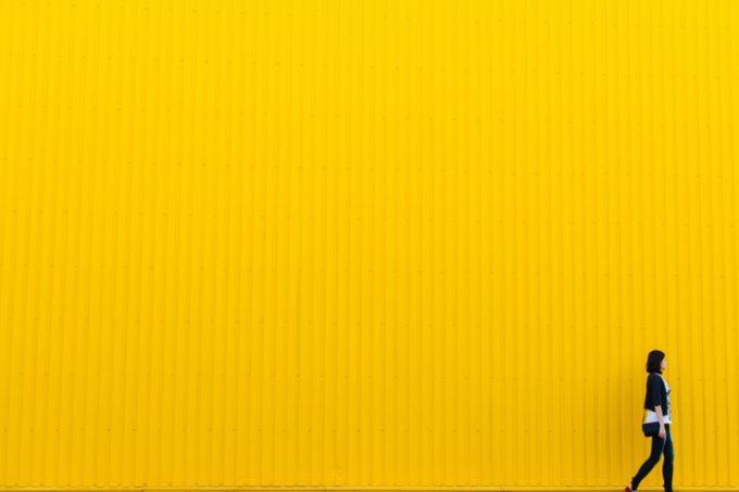 woman-walking-against-yellow-wall